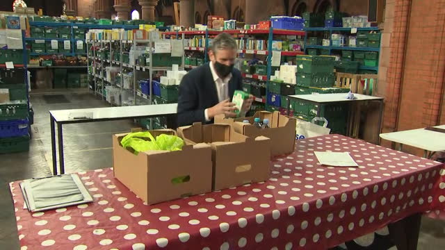 "keir starmer, labour leader, visits food bank and helps pack up food parcels - ""bbc news"" stock videos & royalty-free footage"