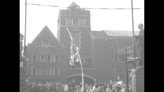 keith brown of yale pole vaults at university of pennsylvania's franklin field, spectators in front of field house in background / note: exact day... - ivy league university stock videos & royalty-free footage