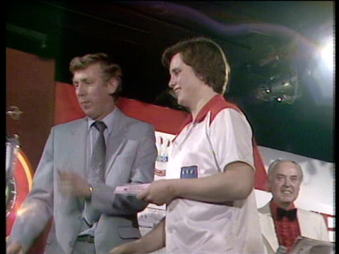 Keith Deller steps forward to collect winner's cheque for £8000 and lift World Darts Championship trophy Jollees Cabaret Club StokeonTrent 1983
