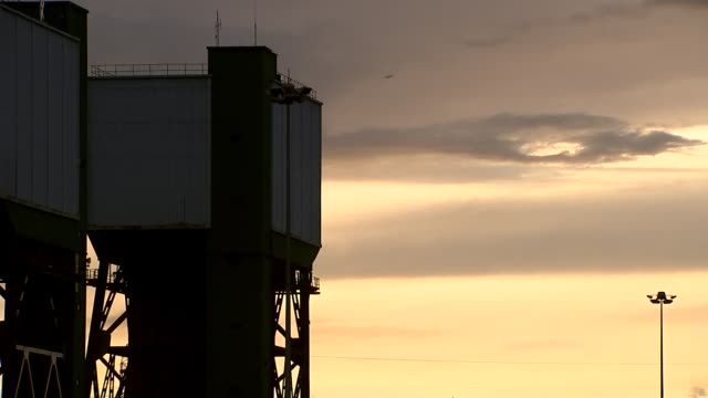north yorkshire beal kellingley ext kellingley colliery building exterior / small chimney and bare trees / various of sky over colliery structures at... - kohlengrube stock-videos und b-roll-filmmaterial