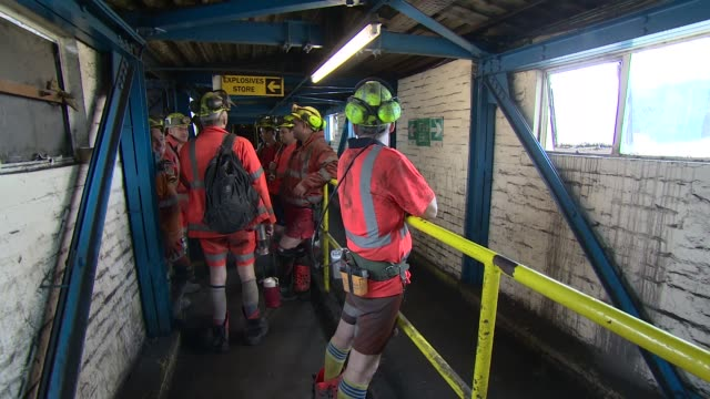 colliery and miners miners in locker room putting on protective clothing / workers preparing for shift / miners along corridor / sign 'safety... - mine shaft stock videos and b-roll footage