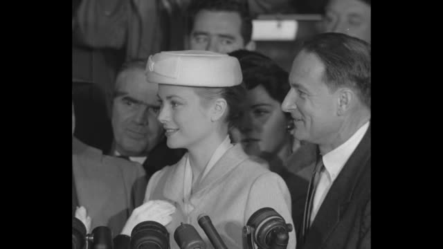 kelly stands at array of microphones hear press shouting / vs beauty shots monaco ws peninsula soldiers marching street festooned with flags - grace kelly actress stock videos and b-roll footage