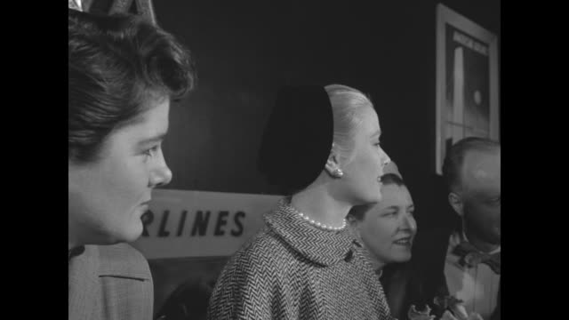 kelly wearing a tweed coat and pearls and holding a corsage is photographed and speaking with reporters / as she's surrounded by people she enters a... - grace kelly actress stock videos and b-roll footage