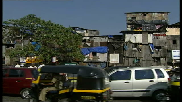 ken livingstone visits bollywood film set india mumbai ext busy traffic along past shanty town dwellings large glass office block and seafront... - bollywood stock videos and b-roll footage