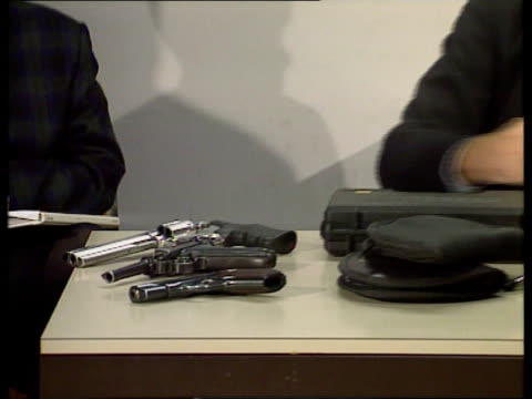stockvideo's en b-roll-footage met guns stolen anat england kent cms det supt nick biddiss places gun on table at pkf tilt - crime and murder
