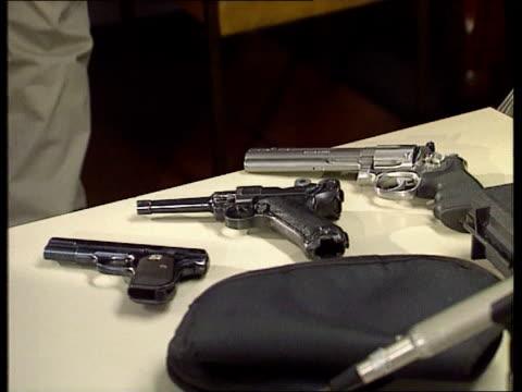 stockvideo's en b-roll-footage met guns stolen bc4n england kent cms det supt nick biddiss places gun on table at pkf tilt cms handguns on table c4n - crime and murder