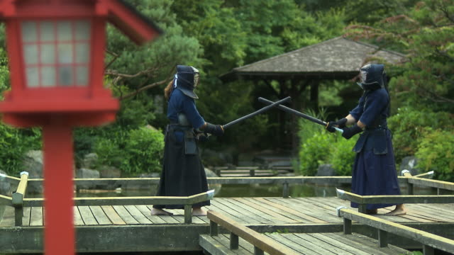 kendo fighter fighting in a park - 攻撃的点の映像素材/bロール