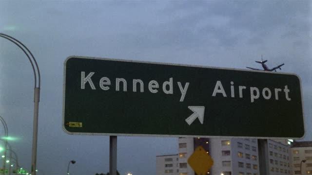 vídeos de stock, filmes e b-roll de 1969 cu la kennedy airport sign at dusk, plane flying overhead, new york city, new york, usa - placa de estrada