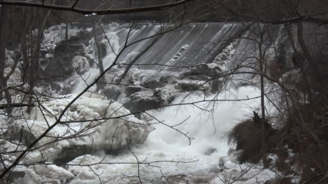 Kent Connecticut Fast moving water caused by the rapid melting of ice jams flows over Bulls Bridge Dam and cascades over ice covered rocks along the...