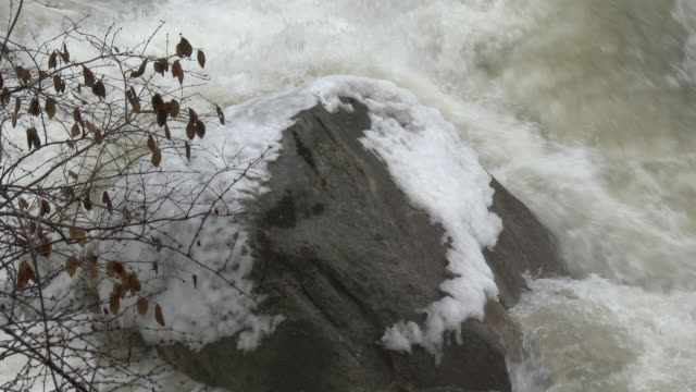 Kent Connecticut Fast moving water caused by the rapid melting of ice jams cascades over ice covered rocks along the Housatonic River