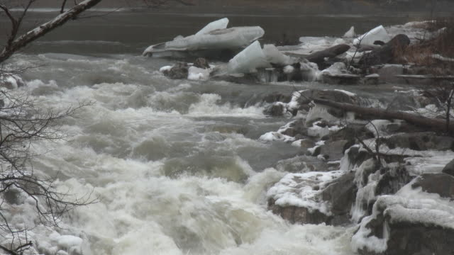 Kent Connecticut Light rain falls as fast moving water flows over rocks covered in thick ice along the Housatonic River