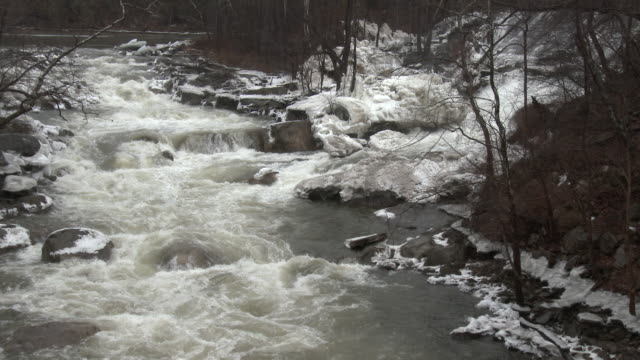 Kent Connecticut Thick ice covers rocks along the Housatonic River as fast flowing river water caused by the rapid melting of ice jams flows...