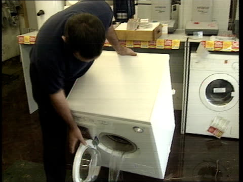 kent flooding kent flooding itn gv ruined stock in food shop pan rl ms man empties water from washing machine in shop cms shop owner brian carrott... - man and machine stock videos & royalty-free footage