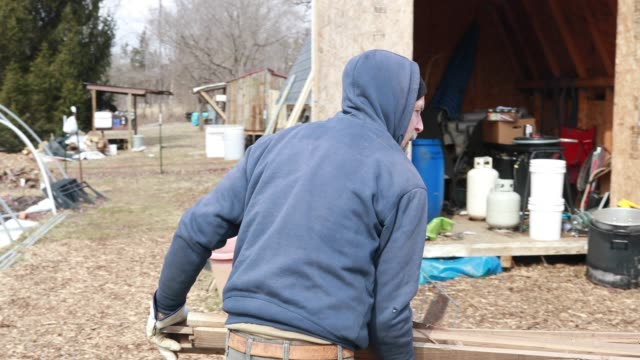 Kent Macpherson puts more wood on a fire as he helps make wood fired maple syrup at the Knightridge Farmstand Sunday March 10 2019 Macpherson said...