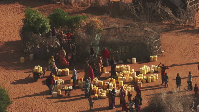 kenya, dabaab: people with canisters of water - refugee camp stock videos & royalty-free footage