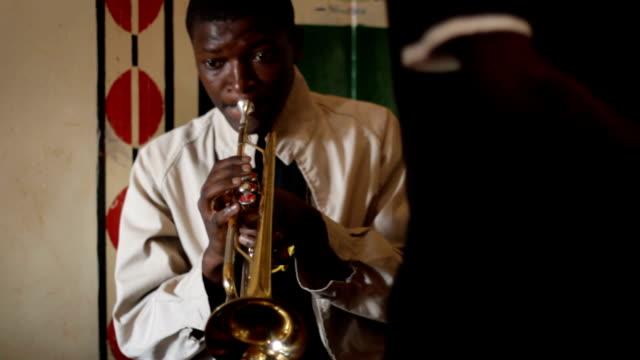 vídeos de stock, filmes e b-roll de kenya, nairobi, korogocho slum, ghetto classic music band - só um menino adolescente