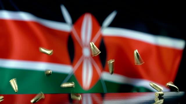 kenyan flag behind bullets falling in slow motion - kenyan flag stock videos & royalty-free footage