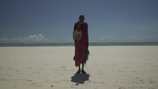 vídeos de stock, filmes e b-roll de kenyan maasai posing on beach - cultura indígena