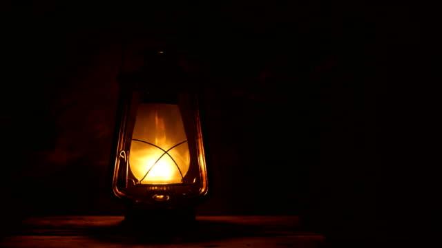 vidéos et rushes de lampe à pétrole avec le vieux mur en bois - lampe électrique