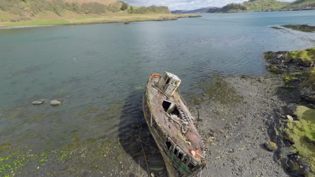 kerrera island scotland, aerial view of coastline with old boat and oban in the background - coastal feature stock videos & royalty-free footage