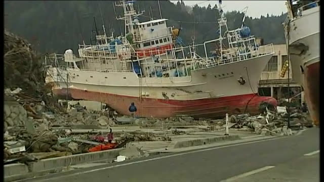 young japanese woman away through debris pull out huge ships piled together, one on roadway ships stranded on broken debris of other buildings and... - earthquake stock videos & royalty-free footage
