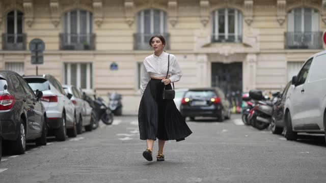 ketevan giorgadze @katie.one wears a white crop tie waist shirt by le ger, a pleated satin lustrous midi black skirt by selezza london, black leather... - satin stock videos & royalty-free footage