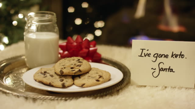 """ketogenic christmas: panning shot of santa politely refusing milk and cookies by placing a """"i've gone keto"""" note by the fireplace on christmas eve - tray stock videos & royalty-free footage"""