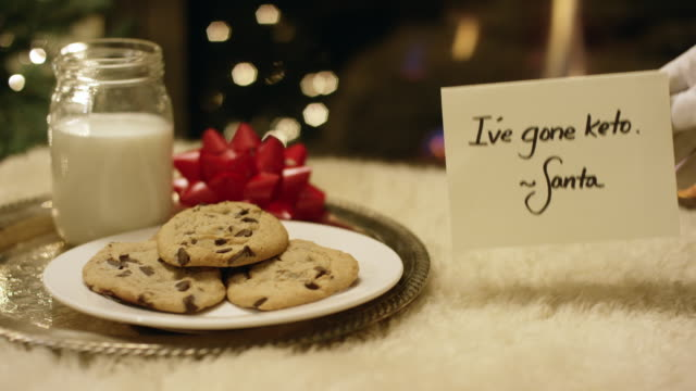 """ketogenic christmas: santa politely refuses milk and cookies by placing a """"i've gone keto"""" note by the fireplace on christmas eve - biscuit stock videos & royalty-free footage"""
