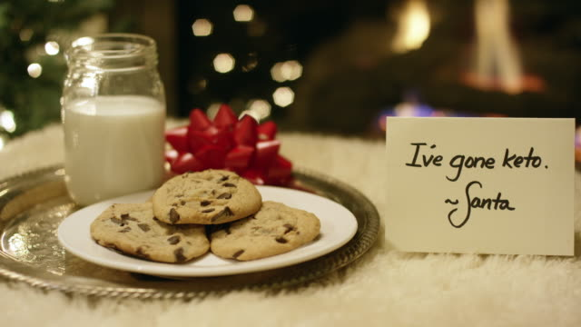 "ketogenic christmas: santa politely refuses milk and cookies with a ""i've gone keto"" card by the fireplace on christmas eve - low carb diet stock videos & royalty-free footage"