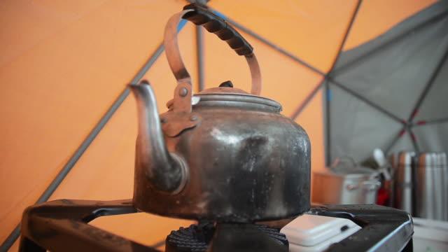 kettle on stove - キャンプ用ストーブ点の映像素材/bロール