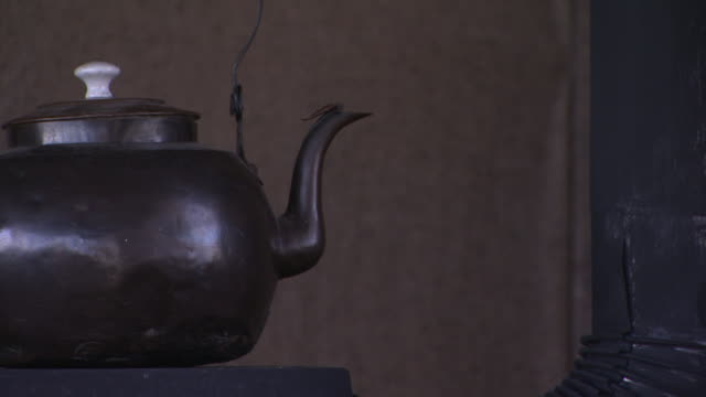 cu kettle tea coffee on oldfashioned black stove partial pipe on right wooden wall w/ crack bg 1910s - tea kettle stock videos & royalty-free footage