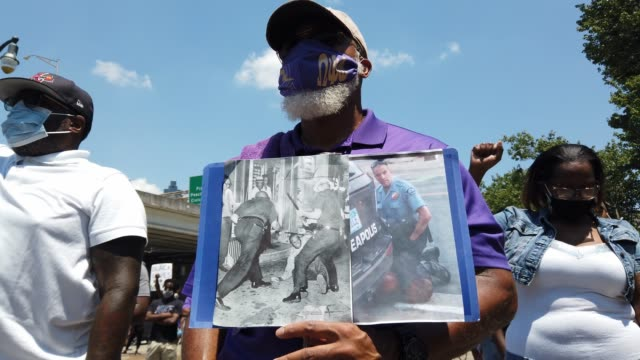 kevin holds a poster showing a minneapolis police officer as he kneels on george floyd's neck leading to his death while he stands with other people... - poster stock videos & royalty-free footage