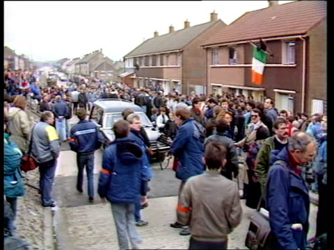 Kevin McCracken IRA funeral NORTHERN IRELAND Belfast TMS Mourners gather outside house tricolour flying from window CMS Mourners BV Mourners TV...