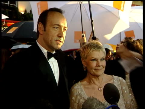 old vic/phone robbery; lib kevin spacey with judi dench talking to press as they arrive at the baftas - ジュディ・デンチ点の映像素材/bロール