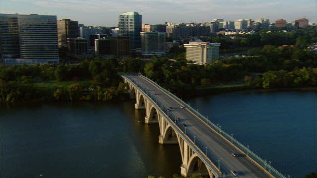 vídeos de stock e filmes b-roll de aerial key bridge on potomac river and high-rise offices of rosslyn, washington d.c., usa - arlington virgínia