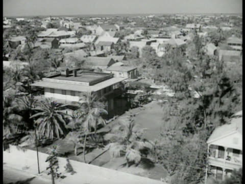 key west neighborhood houses people walking out of wpa offices two unidentified men working at desk possibly architects working on papers - new deal video stock e b–roll