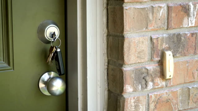 Keys in door , Silver Door Knob , and Brick Home