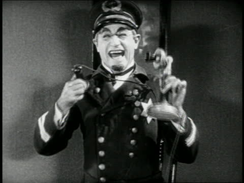 b/w 1924 keystone kop dispatcher (will rogers) laughing + putting phone down on desk / feature - feature phone stock videos and b-roll footage