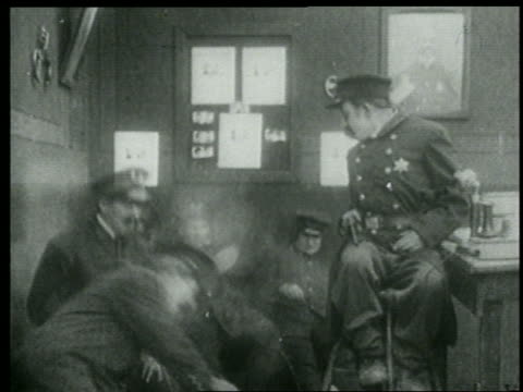stockvideo's en b-roll-footage met b/w 1915 keystone kop dispatcher on stool waking sleeping kops by shooting gun into floor - 1915