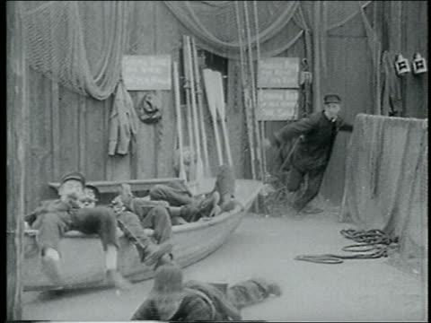 b/w 1915 keystone kop diving onto legs of 2nd kop being dragged by end of rope on pier / feature - 1915年点の映像素材/bロール