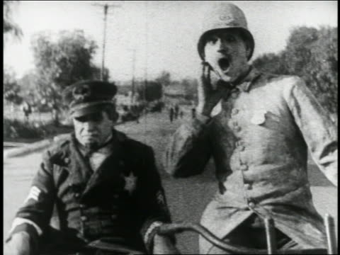 b/w 1924 keystone kop driving 2nd kop (will rogers) on motorcycle with sidecar on street / feature - sidecar stock videos & royalty-free footage