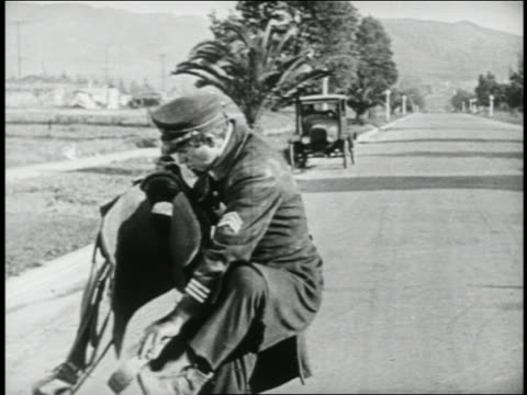 b/w 1924 keystone kop (will rogers) holding saddle + trying to mount horse which is no longer there - 1924年点の映像素材/bロール