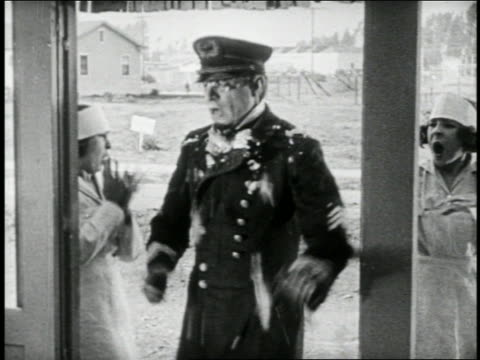 b/w 1924 keystone kop (will rogers) in doorway talking to someone offscreen + is hit in face with food - 1924 stock videos & royalty-free footage