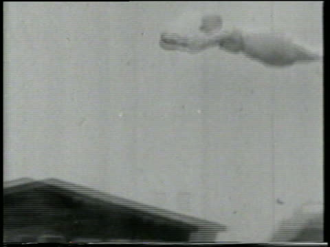 B/W 1915 Keystone Kop in nightgown holding on to smoking cannon ball flying above buildings
