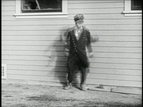 b/w 1924 keystone kop (will rogers) jumping by building + running offscreen / feature - 1924 stock videos and b-roll footage