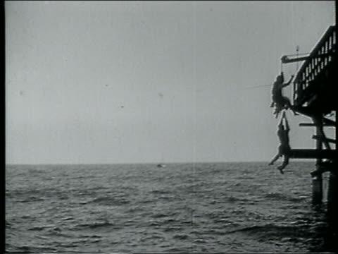 b/w 1915 keystone kop losing grip of dangling woman's leg + falling into ocean / feature - 1915年点の映像素材/bロール