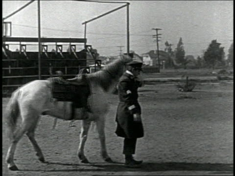 b/w 1924 keystone kop (will rogers) mounting horse with reverse-motion trick + riding away / 3 shots - 1924 stock-videos und b-roll-filmmaterial
