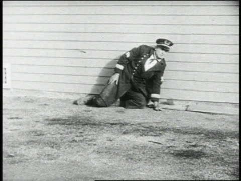 b/w 1924 keystone kop (will rogers) rolling on ground + standing up against building / feature - 1924 stock videos and b-roll footage