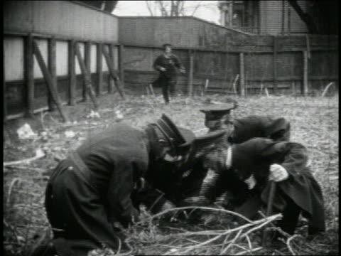b/w 1915 keystone kop rousing group of kops gambling with dice in straw / kops running + climbing wall - gambling stock videos & royalty-free footage