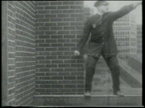 stockvideo's en b-roll-footage met b/w 1915 keystone kop standing on building ledge pointing + shouting / short - 1915